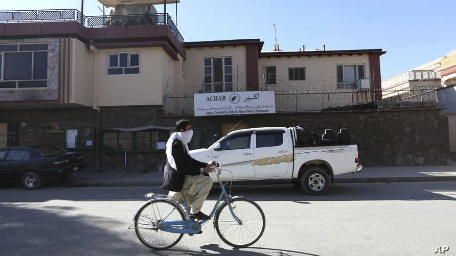 FILE - An Afghan man rides his bicycle in front of the office of the Agency Coordinating Body for Afghan Relief (ACBAR) in Kabul, Afghanistan, Nov. 6, 2016. Criminal gangs in Afghanistan often kidnap foreign aid workers, sometimes selling them to ins