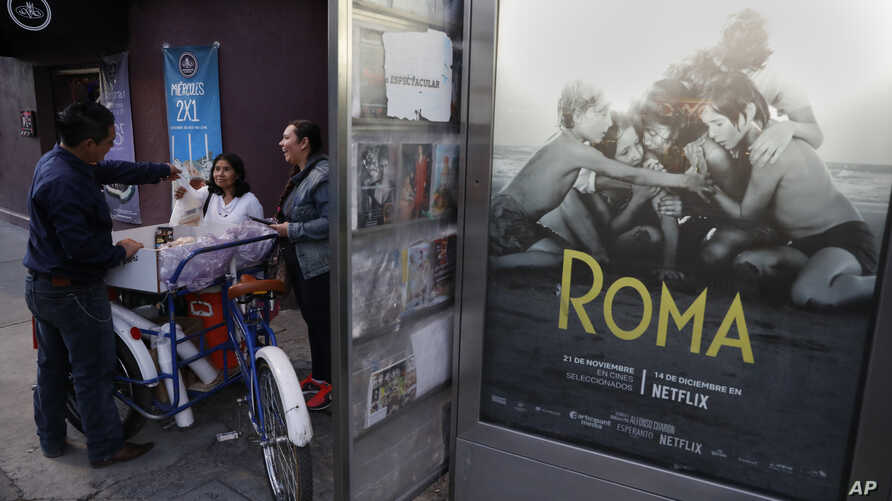 "Women buy pastries and sandwiches from a bicycle vendor in the Roma Sur neighborhood of Mexico City, Wednesday, Dec. 19, 2018, near a newspaper kiosk where Alfonso Cuaron's film ""Roma"" is advertized."
