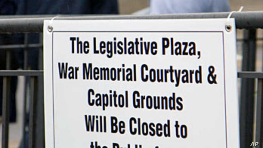 State workers walk away after attaching a sign announcing a new curfew to a fence near the state Capitol in Nashville, Tennessee, Oct. 27, 2011