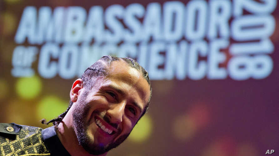 Former NFL quarterback and social justice activist Colin Kaepernick poses with guests after receiving the Amnesty International Ambassador of Conscience Award for 2018 in Amsterdam, April 21, 2018.