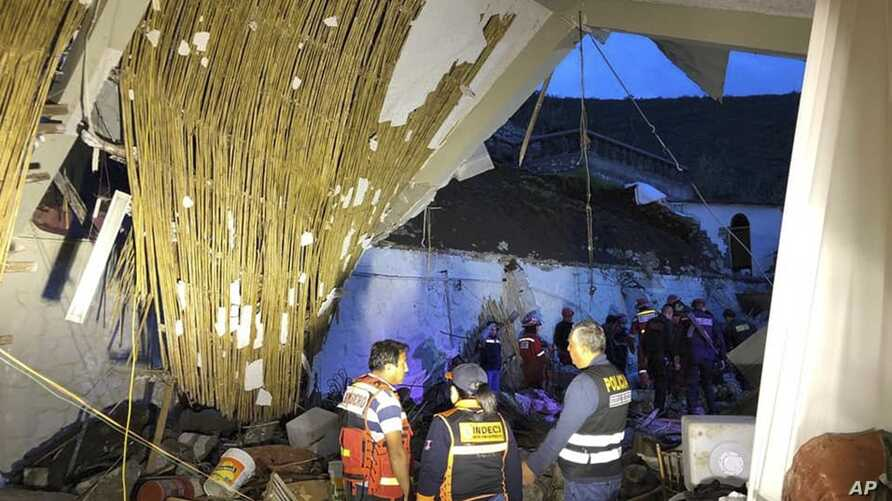 In this photo provided by Abancay police, officers and firefighters stand by a collapsed area of the Alhambra hotel in Abancay, Peru, Jan. 27, 2019.