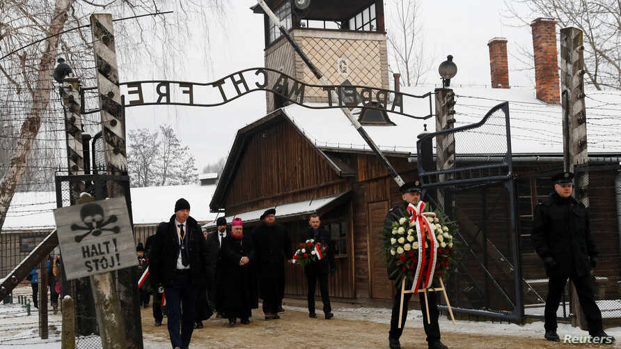 "People arrive to lay wreaths at the ""death wall"" at the former Nazi German concentration and extermination camp Auschwitz, during the ceremonies marking the 74th anniversary of the liberation of the camp and International Holocaust Victims Remembranc"