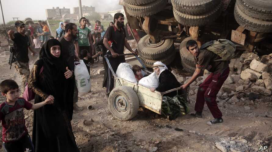 In this Wednesday, May 10, 2017 photo, an elderly woman and a child are pulled on a cart as civilians flee heavy fighting between Islamic State militants and Iraqi special forces in western Mosul, Iraq. (