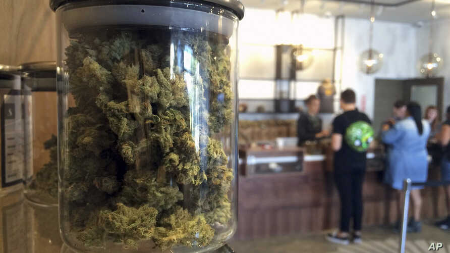 FILE - In this April 20, 2016, photo, customers buy products at the Harvest Medical Marijuana Dispensary in San Francisco. In November, the state's voters will decide whether to legalize the drug's recreational use.