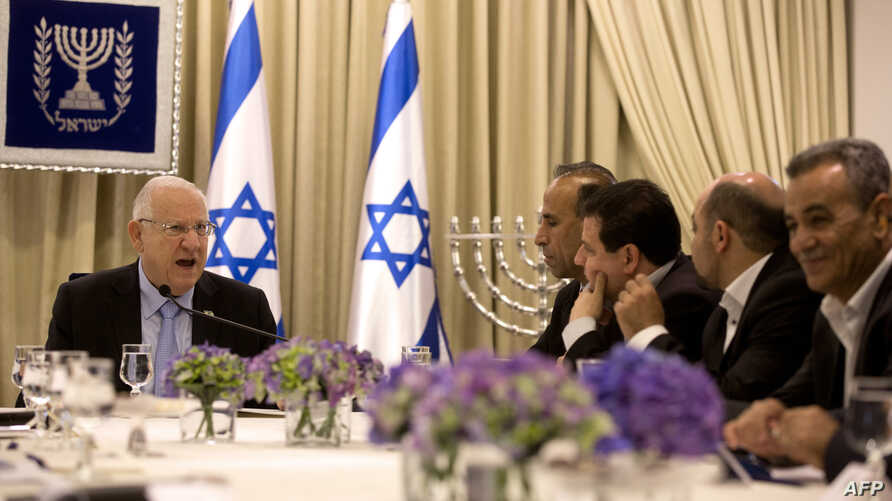 Israeli President Reuven Rivlin, left, speaks during consultations with representatives of the Joint List, right, an alliance of four small Arab-backed parties, to hear whom they would recommend for prime minister at his residence in Jerusalem, March