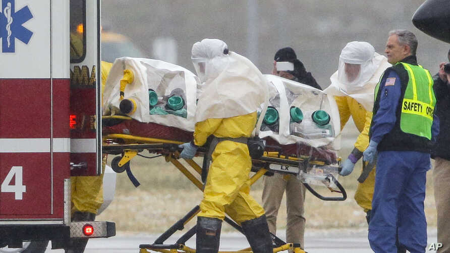 Health workers in protective suits transport Dr. Martin Salia, a surgeon working in Sierra Leone who had been diagnosed with Ebola, at Nebraska Medical Center in Omaha, Neb., Nov. 15, 2014.