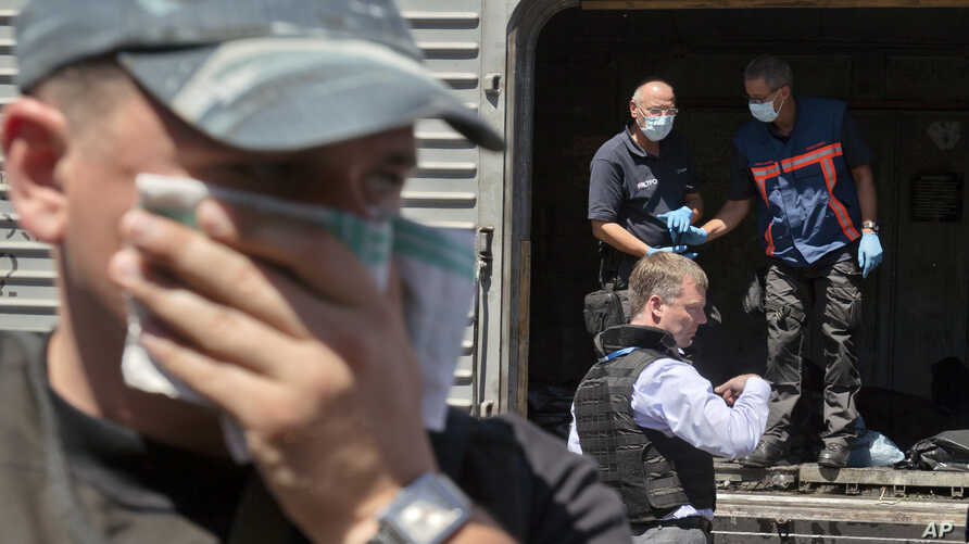 A man covers his face with a rag as deputy head of the OSCE mission to Ukraine Alexander Hug stands outside a refrigerated train as members of Netherlands' National Forensic Investigations Team inspect bodies, seen in plastic bags, Torez, eastern Ukr...
