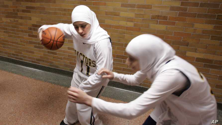 FILE - Fordson High School basketball player Fatima Kobeissi, (11) warms up in the hallway with teammate Hyatt Bakri before the basketball game against Willow Run in Dearborn, Mich., Tuesday, Dec. 4, 2007. FIBA announced hijabs will be allowed in int