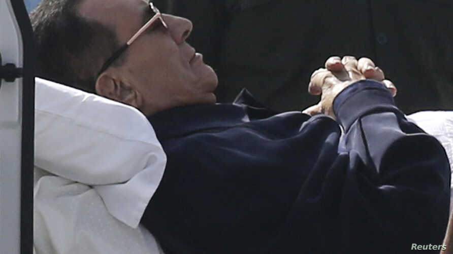 Former Egyptian President Hosni Mubarak lies on a stretcher while being transported ahead of his trial in Cairo, Sept. 27, 2014.