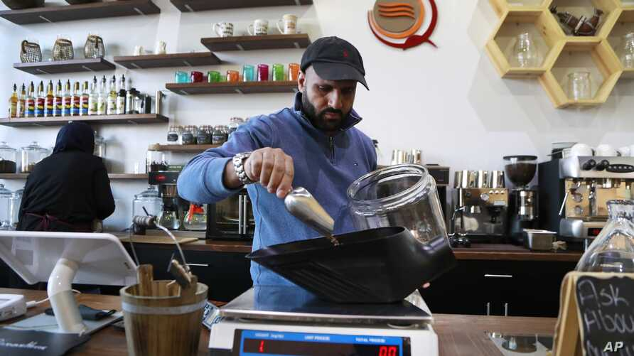 Ibrahim Alhasbani, owner of Qahwah House, a cafe that serves coffee made from beans harvested on his family's farm in Yemen's mountains, measures coffee beans in Dearborn, Michigan, Jan. 9, 2018.