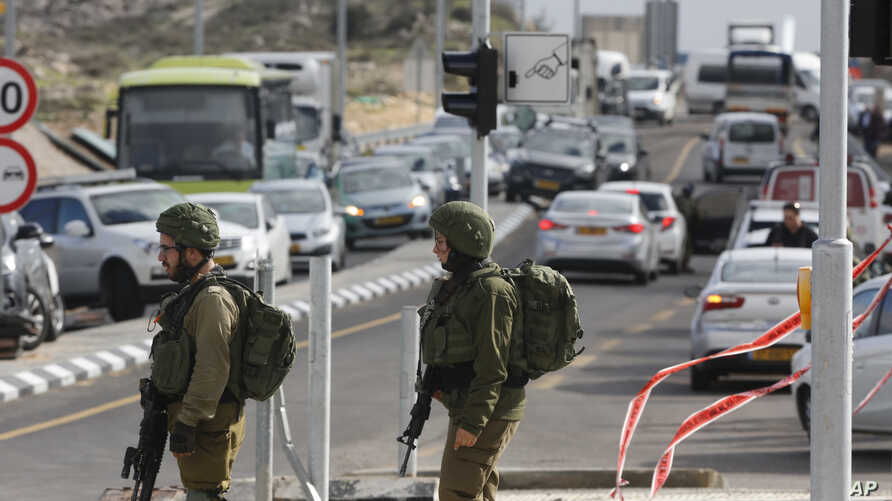 Israeli soldiers stand at the scene of an attack near the settlement of Givat Assaf in the West Bank, Dec. 13, 2018. A Palestinian gunman opened fire at a bus stop outside a West Bank settlement Thursday, killing at least two Israelis before fleeing,
