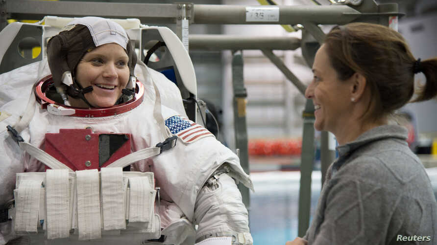 FILE - Astronaut Anne McClain, left, is seen during training at the Neutral Buoyancy Laboratory in Houston, Texas, Jan. 12, 2015.