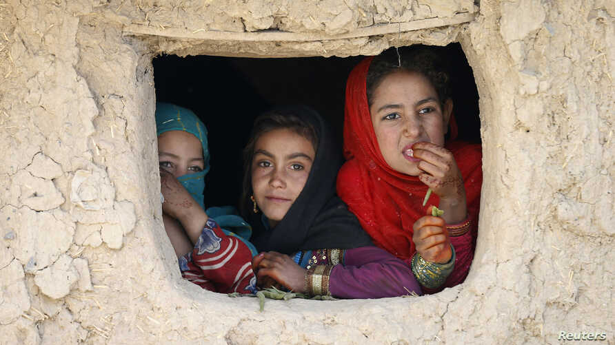 Internally displaced Afghan girls look out from their shelter at a refugee camp in Kabul, Oct. 14, 2014.