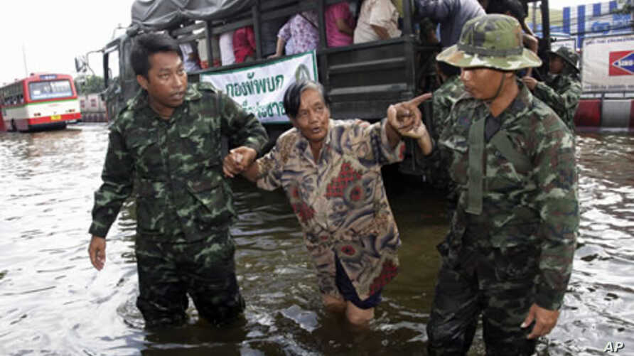 Thai soldiers help people evacuate from a flooded area at Phisi Charoen district in Bangkok, November 2, 2011.