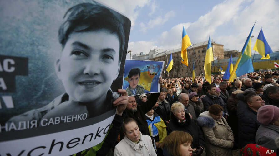 """People hold posters depicting Ukrainian pilot Nadezhda Savchenko, during a interfaith prayer """"For Ukraine, for peace, for Nadezhda"""" in support of Ukrainian pilot Nadezhda Savchenko in Kyiv, Ukraine, March 1, 2015."""