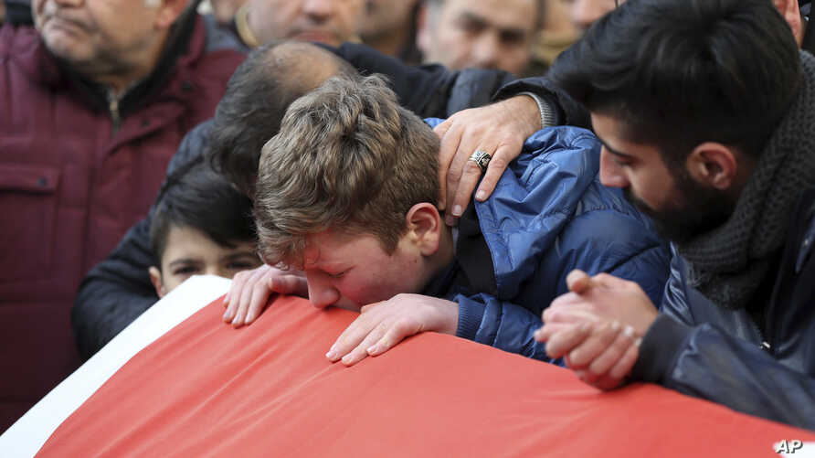 Family members and friends mourn as they attend funeral prayers for Ayhan Akin, one of the nightclub victims, in Istanbul, Jan. 1, 2017.