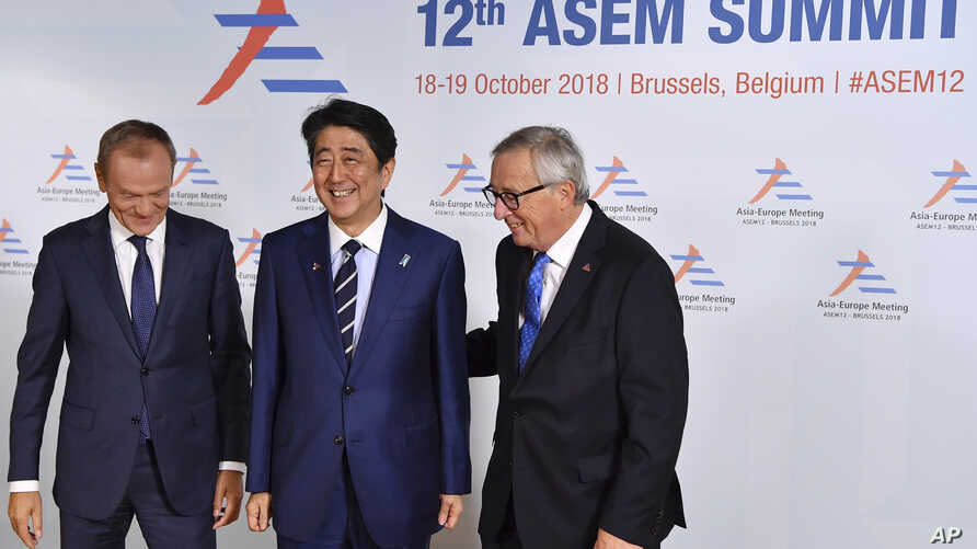 Japan's Prime Minister Shinzo Abe, center, is greeted by European Council President Donald Tusk, left, and European Commission President Jean-Claude Juncker during arrivals for the ASEM 12 in Brussels, Belgium, Oct. 18, 2018.