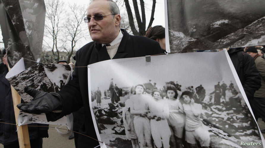 FILE - Holocaust historian Efraim Zuroff stands beside a poster showing Nazi war crimes in Riga, Latvia, March 16, 2012.
