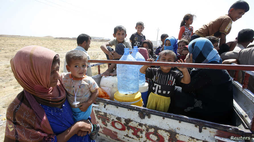 Displaced people from the minority Yazidi sect, who fled from the violence in the Iraqi town of Gwer, wait to return at a check point at the entrance of the town, Aug. 18, 2014.