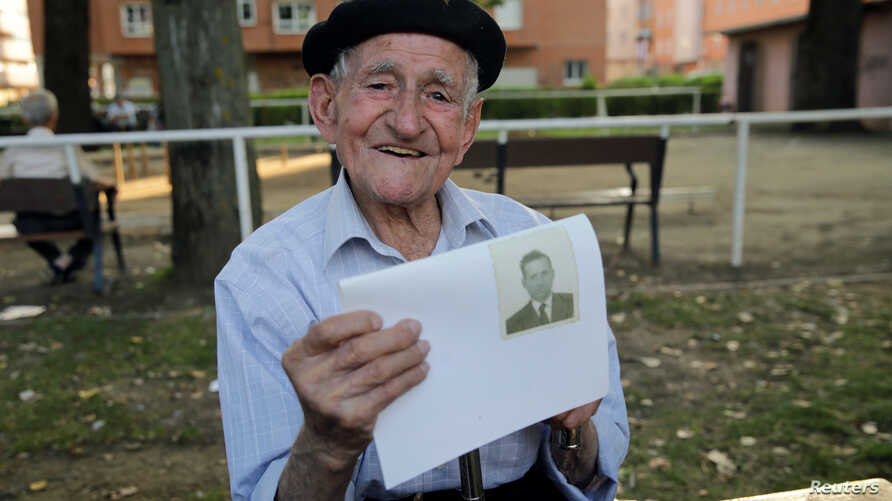 Maximino San Miguel, 102, holds a picture of himself when he was young as he poses for a portrait in a park near his home in Leon, northern Spain, Sept. 3, 2016
