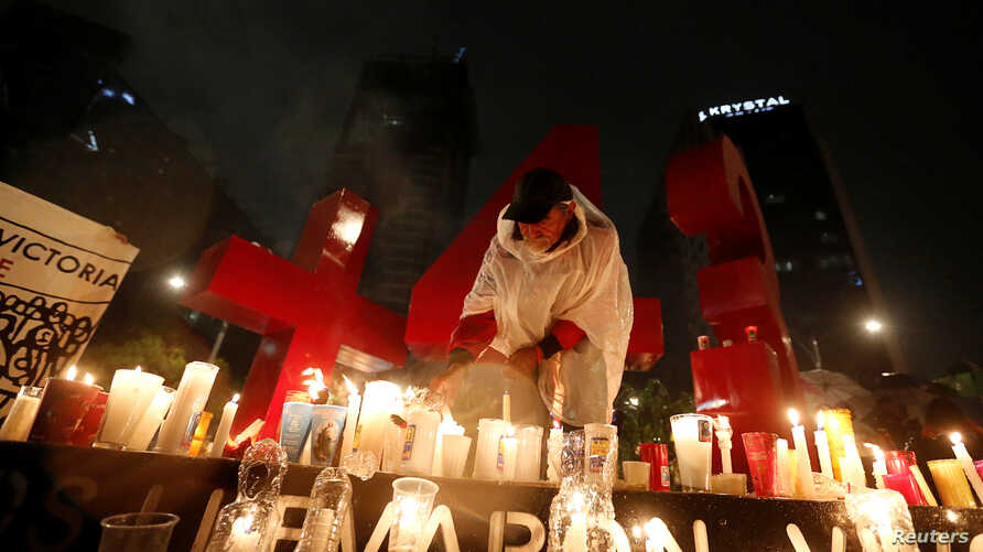 A protester from the National Coordination of Education Workers, a teachers union, places candles in front of a monument of the number 43 during a vigil following clashes in southern Mexico over the weekend between police and members of CNTE, at Refo