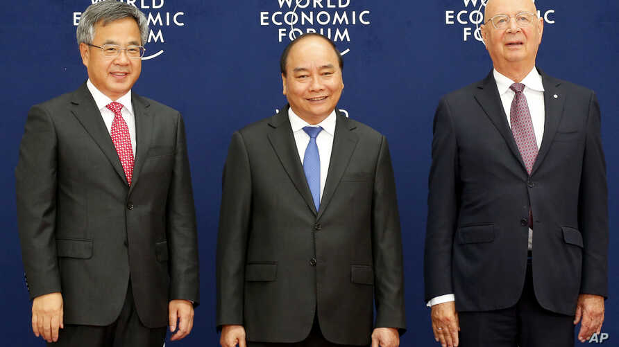 Vietnamese Prime Minister Nguyen Xuan Phuc, center, Chinese Vice Premier Hu Chunhua, left, and Klaus Schwab, executive chair of the World Economic Forum, pose prior to the World Economic Forum on ASEAN Wednesday, Sept. 12, 2018 .