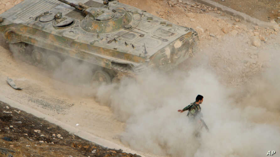 A Syrian APC moves raising dust in Harasta, northeast of Damascus, Syria, Oct. 22, 2015.