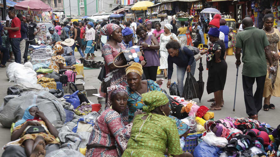 Pedestrians shop at a busy Balogun Market in Lagos, Nigeria, Sept. 5, 2017.  Nigeria announced it will start issuing visas on arrival to all Africans as a way to improve intra-African trade.
