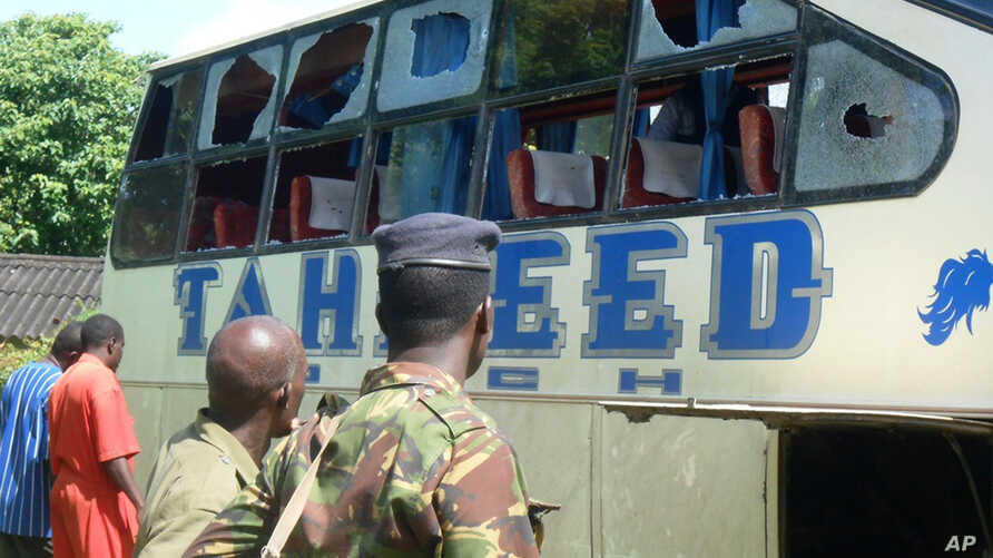 A Kenyan police officer with civilians views a Taheed Bus at the Lamu Police Station in Lamu County, July 19, 2014.