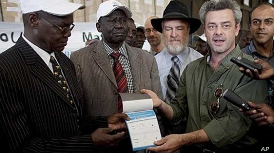 Eamon Omordha, right, Deputy Director of United Nations Integrated Referendum and Electoral Division, hands over a referendum ballot to Justice Chan Reec Madut, left, Chairman of the Southern Sudan Referendum Bureau, during a material handover ceremo