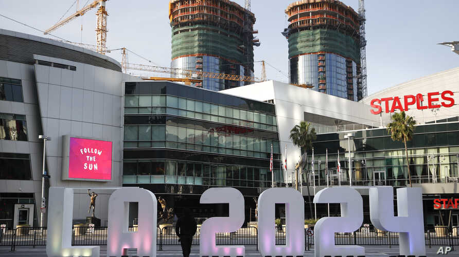 """FILE - A Los Angeles 2024 sign stands in front of Staples Center, in Los Angeles, May 11, 2017. An International Olympic Committee panel has praised Los Angeles and Paris for """"outstanding"""" plans to host the 2024 Summer Games."""