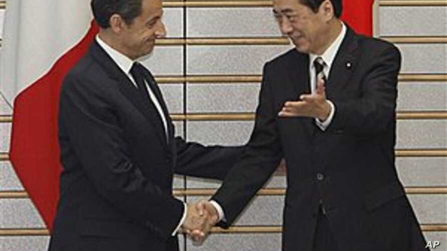 French President Nicolas Sarkozy is welcomed by Japanese Prime Minister Naoto Kan prior to their talks at Kan's official residence in Tokyo, March 31, 2011