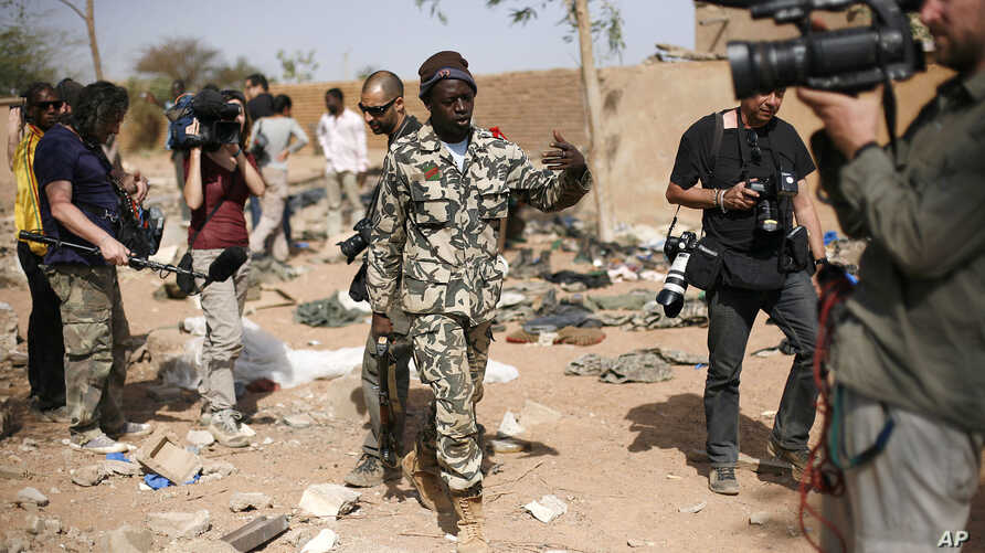 A Malian soldier gestures at journalists to leave the area of a French air strike. Image was taken during an official visit organized by the Malian army to the town of Konna, north of Mali's capital Bamako, January 26, 2013.