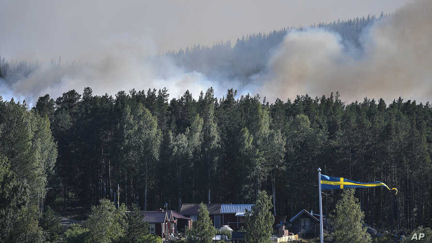 Smoke rises from just beyond a bank of trees and homes, as a wildfire threatens large tracts of land, outside Ljusdal, Sweden, July 17,  2018.