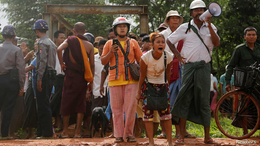 People react as Myanmar authorities demolish huts occupied by thousands of informal settlers to clear the land for development, in Hlegu township outside Yangon, June 12, 2017.