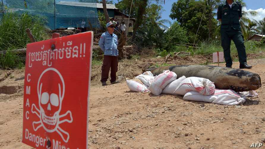 FILE - A Cambodian Mine Action Center (CMAC) member (L) and policeman keep watch behind a Mark 82 bomb in Kandal province on May 21, 2015.