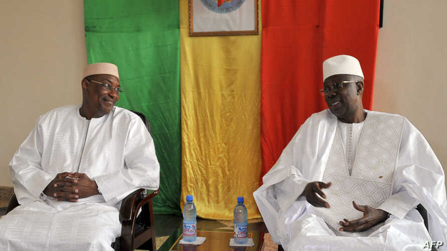Malian newly appointed Prime Minister Abdoulaye Idrissa Maiga (L) listens to his predecessor Modibo Keita (R), April 10, 2017, during the handover ceremony in Bamako, two days after his nomination by Malian President