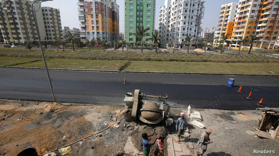 Laborers work at the construction site of a residential complex on the outskirts of Kolkata, India, Jan. 29, 2018.