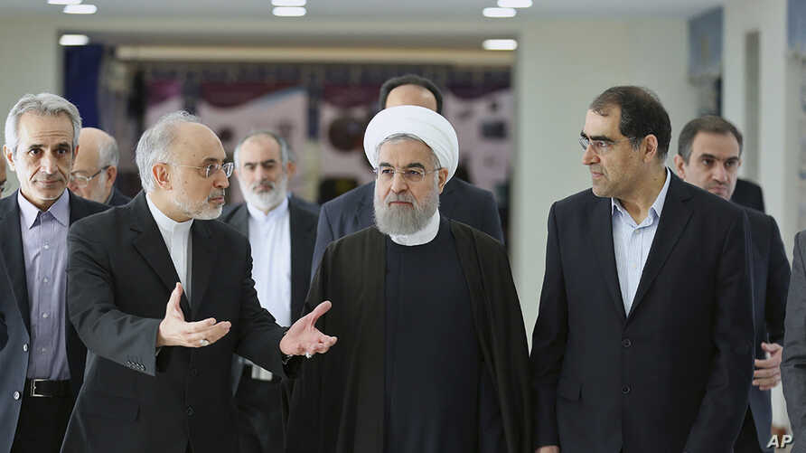FILE - President Hassan Rouhani (center) listens to head of Iran's Atomic Energy Organization Ali Akbar Salehi (left) while attending a ceremony marking the national day of nuclear technology in Tehran, Iran, Thursday, April 7, 2016. Iran's Health M