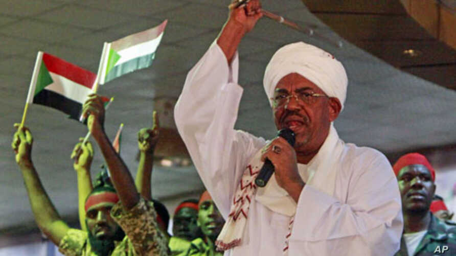 Supporters wave Sudanese flags as Sudanese President Omar al-Bashir addresses supporters during a rally at the ruling National Congress Party  headquarters in Khartoum, Sudan, April 18, 2012.