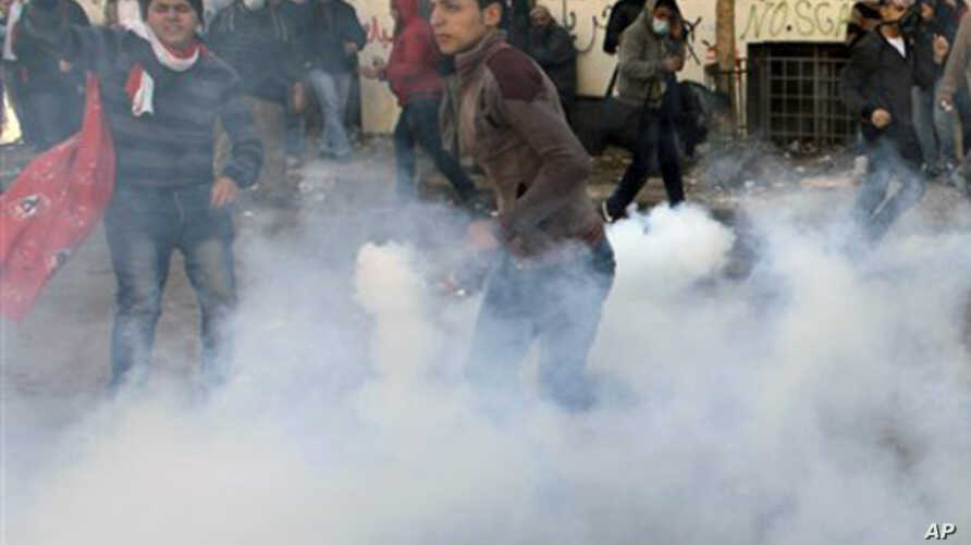 An Egyptian protester throws a tear gas canister fired by security forces during clashes near the Interior Ministry in Cairo, Egypt, Sunday, Feb. 5, 2012.