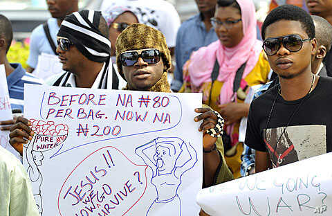 A protester carries a placard during a rally against fuel subsidy cuts in Nigeria's capital, Abuja, January 6, 2012.