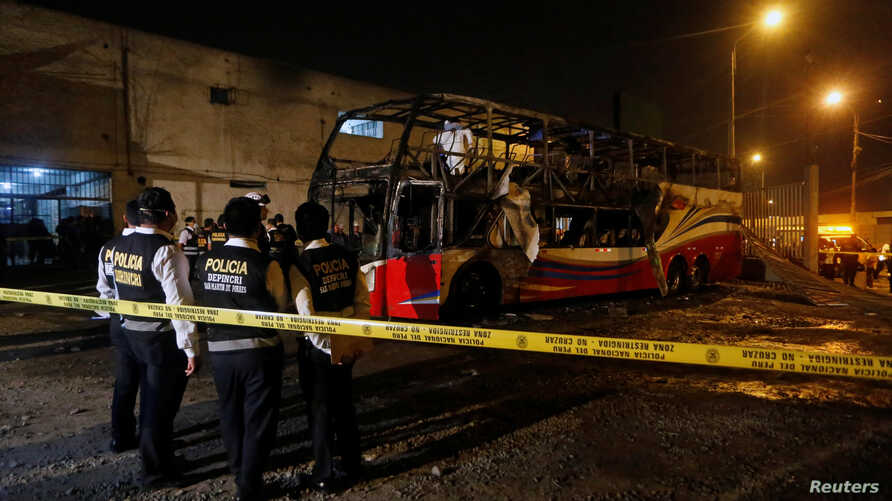 Peruvian police officers work next to a burnt bus on a street in Lima, Peru, March 31, 2019.