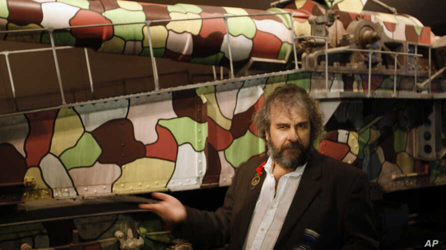 Director Peter Jackson points out a multi-colored cannon used during the early days of the World War I at the museum exhibition he has created, April 17, 2015, in Wellington, New Zealand.