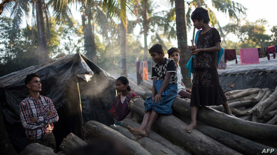 FILE - Rohingya stand on chopped trees in the Naybara refugee camp in Cox's Bazar, Dec. 3, 2017.