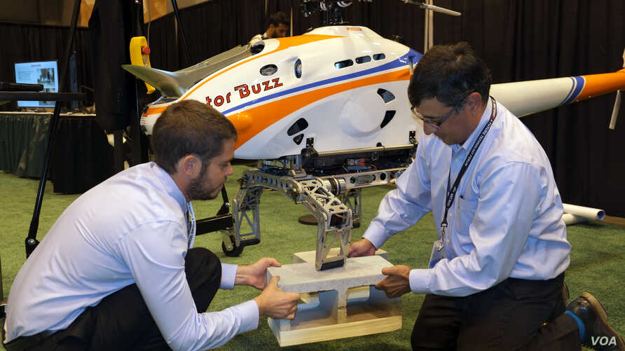 Georgia Tech postdoctoral fellow Mike Ward, left, and DARPA's Ashish Bagai demonstrate how helicopter landing gear respond to obstacles in the landing zone, represented here by concrete blocks. Each leg adjusts independently so the helicopter stays l