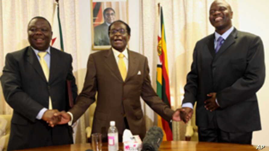 President Robert Mugabe, centre, shares a light moment with Morgan Tsvangirai, left, Zimbabwe's Prime Minister and his Deputy, Arthur Mutambara after giving their end of year message to the nation, at Zimbabwe House in Harare, Wednesday, Dec. 23, 200
