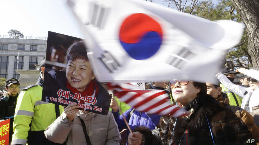 A supporter of impeached South Korean President Park Geun-hye waves flags of the U.S. and South Korea while another holds a portrait of the president during a rally opposing her impeachment in Seoul, South Korea, Feb. 27, 2017.