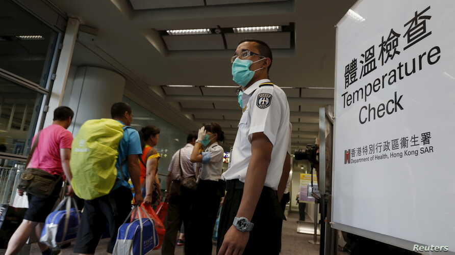 Arriving flight passengers go through a temperature check at Hong Kong Airport as a cautionary measure against Middle East Respiratory Syndrome, June 5, 2015.