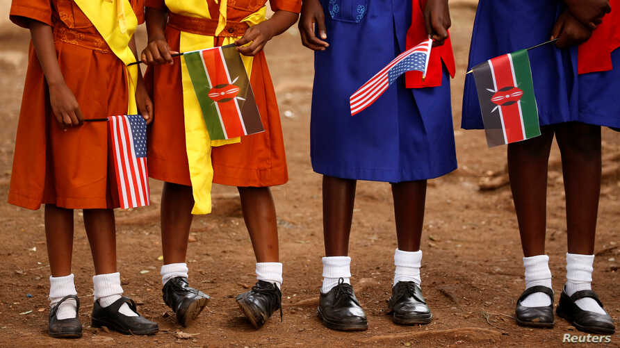 Young girls with U.S. and Kenya flags wait to greet U.S. Ambassador to Kenya Robert Godec as he visits a President's Emergency Plan for AIDS Relief project for girls' empowerment in Nairobi, Kenya, March 10, 2018.